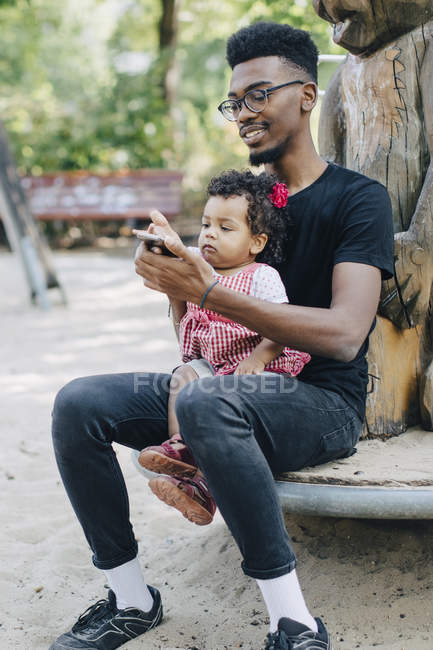 Baby girl using mobile phone while sitting with father on outdoor play equipment at playground — Stock Photo