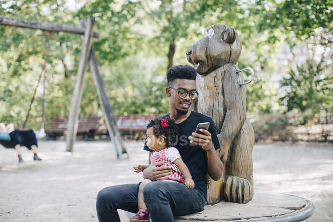 Father using mobile phone while sitting with daughter on outdoor play equipment — Stock Photo