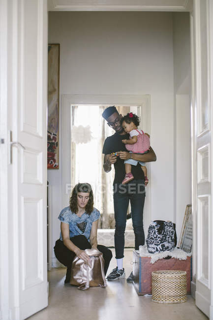 Father carrying daughter while woman packing luggage at home — Stock Photo
