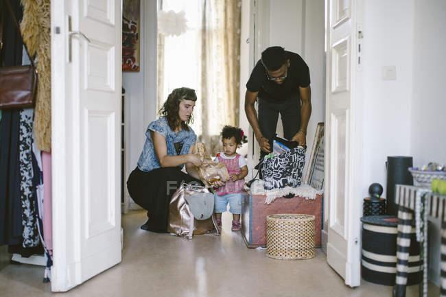 Tochter, Mutter und Vater Verpackung Gepäck zu Hause betrachten — Stockfoto