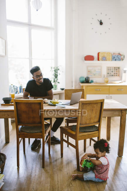Baby girl playing with toy car while father sitting at dining table in house — Stock Photo