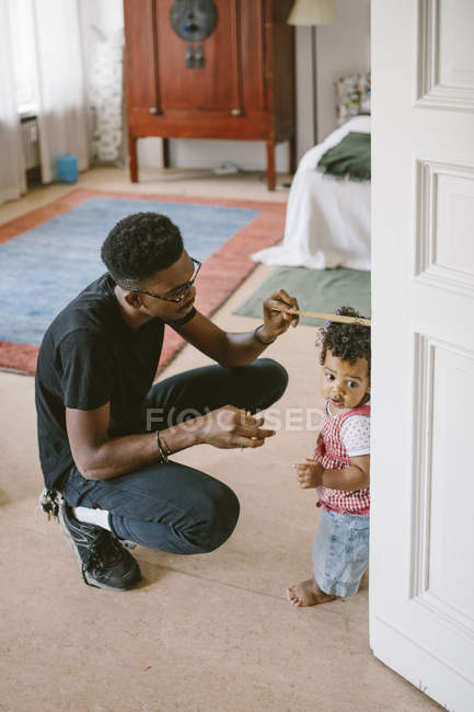 Joven, medir la altura de la hija en casa - foto de stock