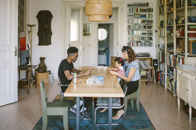 Young man using laptop while woman playing with daughter at dining table in house — Stock Photo