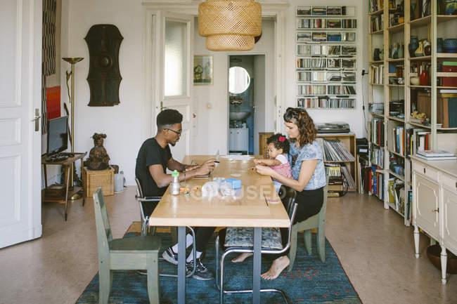 Jovem usando laptop enquanto mulher brincando com a filha na mesa de jantar em casa — Fotografia de Stock