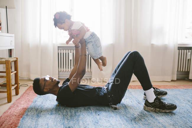 Verspielte Vater Tochter beim liegen auf dem Teppich zu Hause heben — Stockfoto