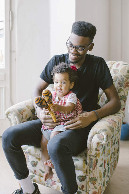 Playful baby girl playing holding maracas while sitting with father on armchair at home — Stock Photo