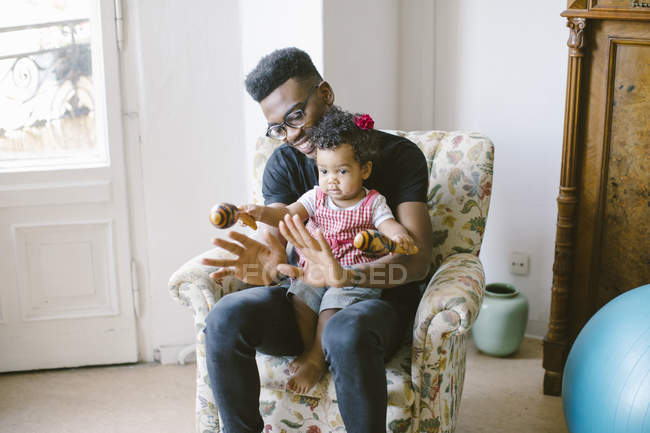 Baby girl holding maracas while sitting with father on armchair at home — Stock Photo