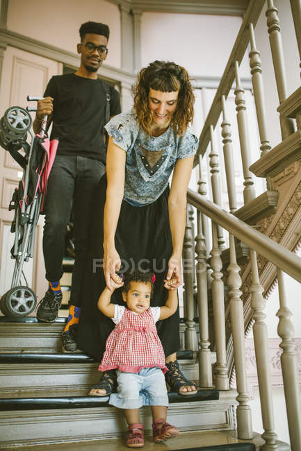 Mother holding hands of daughter moving down on steps in apartment — Stock Photo