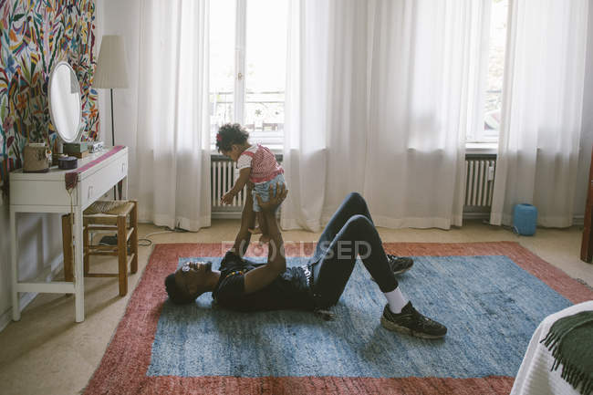 Playful father lifting daughter while lying on carpet at home — Stock Photo