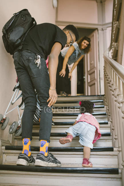 Father and mother looking at baby girl climbing steps in apartment — Stock Photo