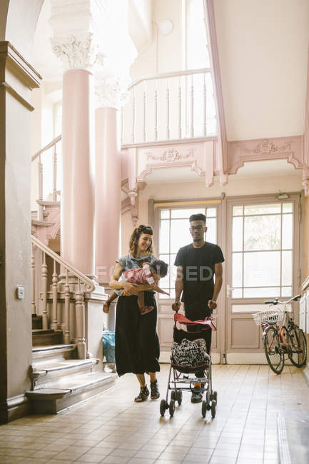 Father pushing baby stroller while woman carrying daughter in apartment — Stock Photo