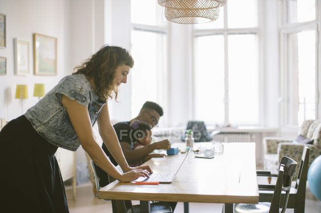Woman using laptop while father playing with daughter at table in house — Stock Photo