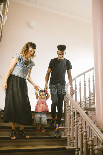 Full length of family moving down on staircase in apartment — Stock Photo