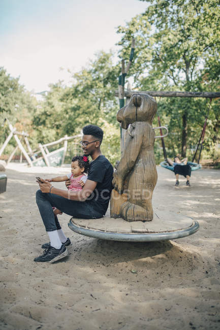 Young man using mobile phone while sitting with daughter on outdoor play equipment — Stock Photo