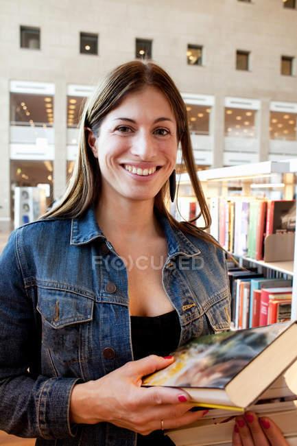 Porträt der Frau mit Stapel Bücher in der Bibliothek — Stockfoto