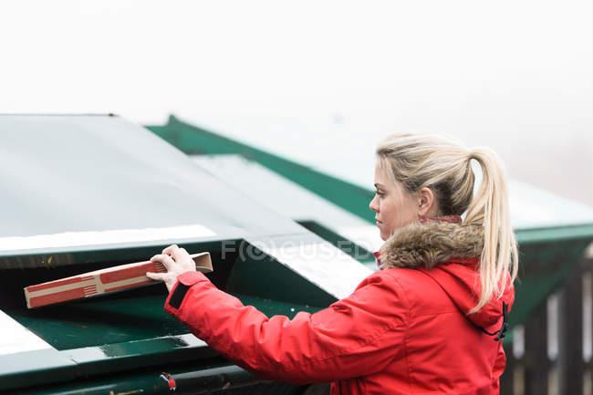 Jeune femme jetant la boîte dans la poubelle — Photo de stock