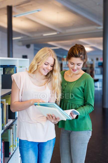Teenage girls reading book in school library — Fotografia de Stock