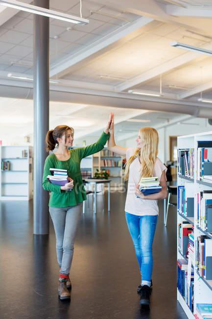 Integrale delle studentesse dando il cinque nella biblioteca della scuola — Foto stock