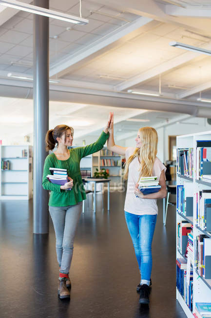 Full length of female students giving high-five in school library — Fotografia de Stock