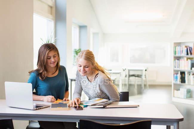 Adolescenti che utilizzano il cellulare a tavola nella biblioteca della scuola — Foto stock