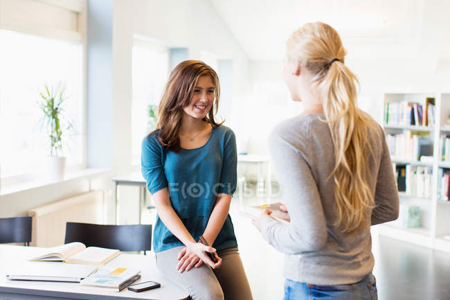 Ragazze adolescenti conversando nella biblioteca della scuola — Foto stock