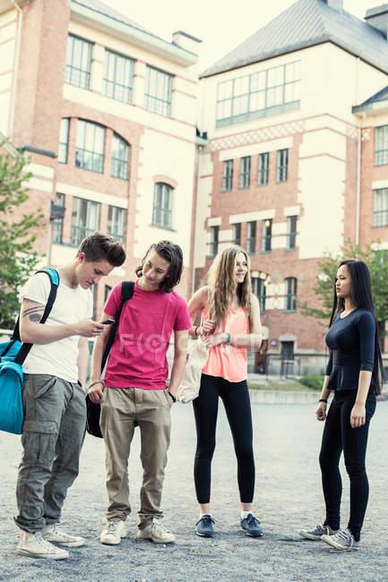 Piena lunghezza di studenti maschi e femmine in piedi sul cortile della scuola superiore — Foto stock