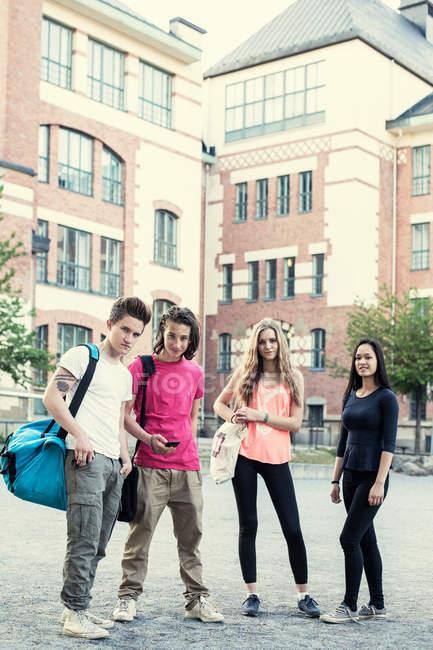 Ganzkörperporträt eines selbstbewussten Gymnasiasten, der auf dem Schulhof steht — Stockfoto