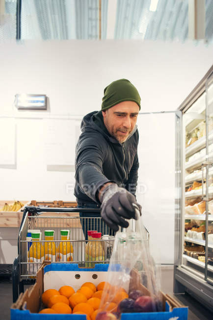 Male worker picking plastic bag with apples from cardboard box at supermarket — Stock Photo