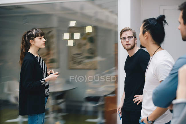 Male and female programmers discussing over adhesive notes stuck on glass in office — Stock Photo