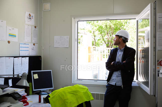 Thoughtful art director standing with arms crossed while looking through window at office — Stockfoto