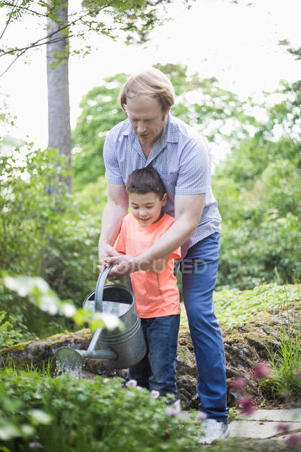 Father and son watering plants with can in back yard — Photo de stock
