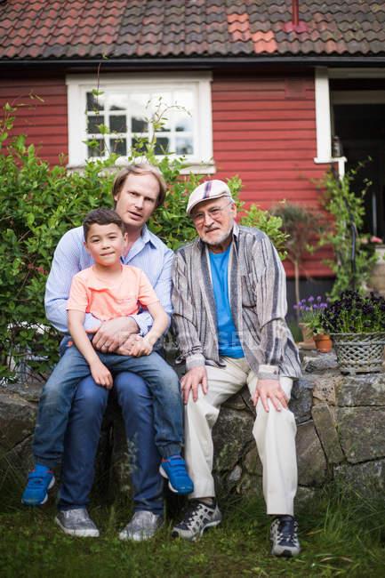 Ritratto di uomo seduto con padre e figlio contro casa nel cortile sul retro — Foto stock