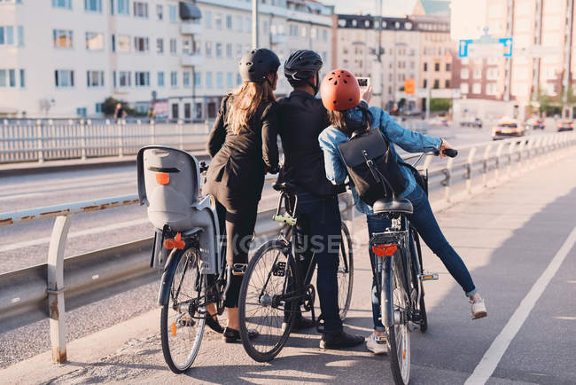 Rear view of man taking selfie with female friends with bicycles on street — Stock Photo