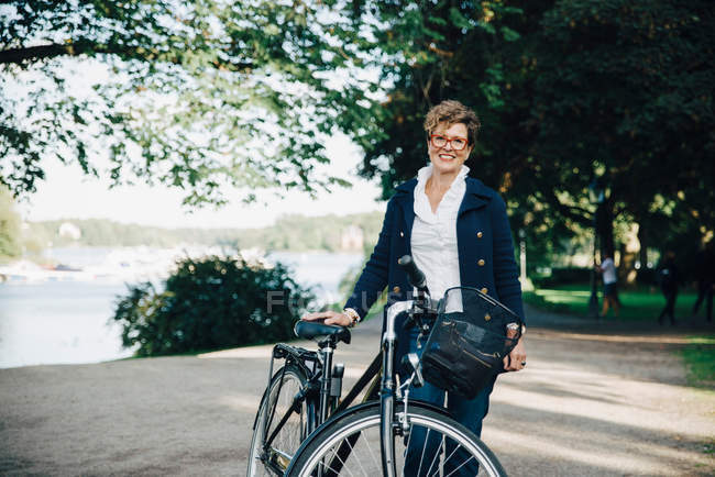 Portrait of smiling senior woman with bicycle standing in park — Stock Photo