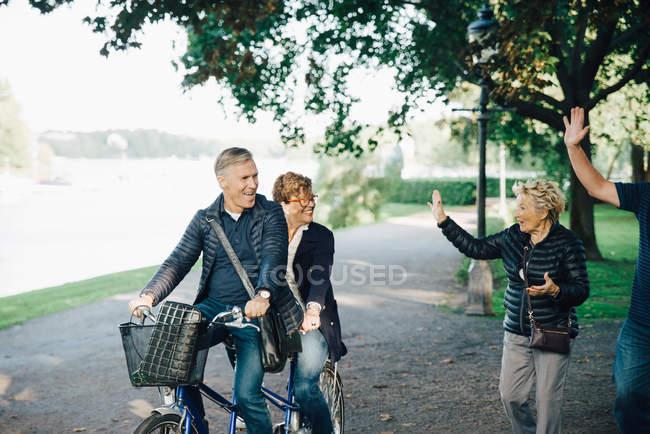 Senior couple waving friends riding tandem bike in park — Stock Photo
