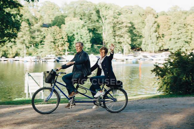 Senior couple enjoying tandem bike ride by pond in park — Stock Photo