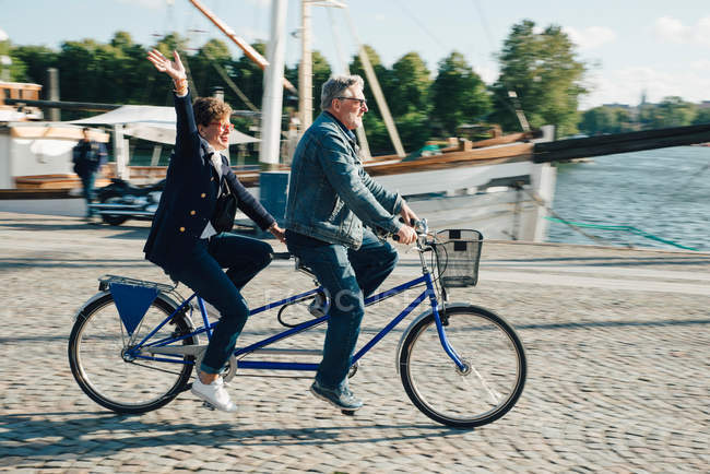 Full length side view of senior couple riding tandem bike on road in city during vacation — Stock Photo