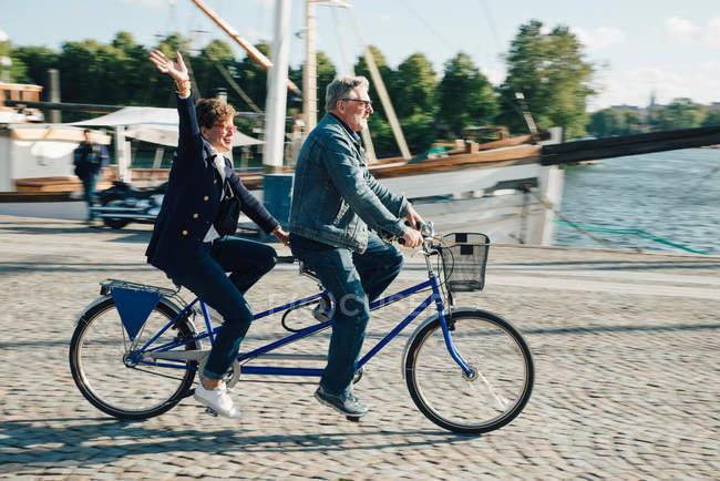 Вид сбоку в полный рост пожилой пары, катающейся на тандемном велосипеде по дороге в городе во время отпуска — стоковое фото