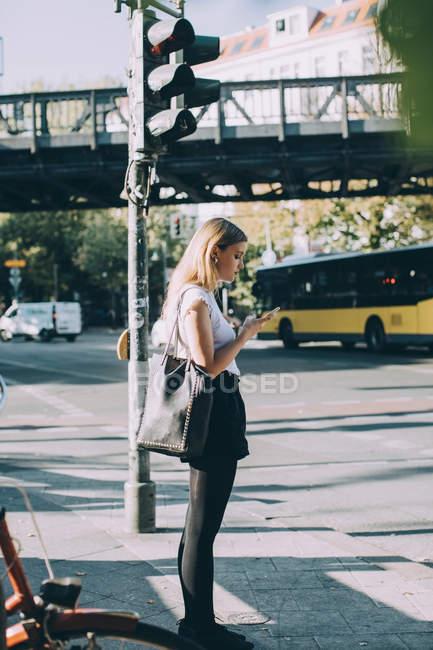 Vista lateral de la mujer joven usando el teléfono móvil mientras está de pie en la acera - foto de stock