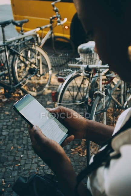 Young woman text messaging through mobile phone while standing on sidewalk in city — Stock Photo