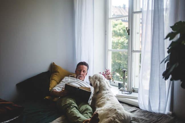 Uomo anziano sdraiato con cane mentre leggeva libro sul letto dalla finestra a casa — Foto stock