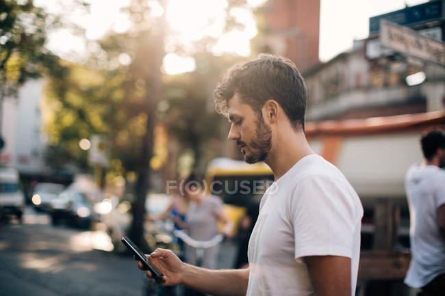 Вид сбоку молодого человека, пользующегося мобильным телефоном, стоя на улице в городе — стоковое фото