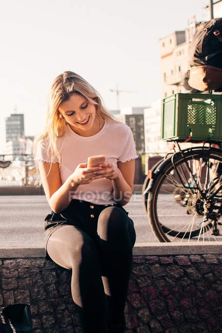 Smiling young woman using mobile phone while sitting on retaining wall at street in city — Stock Photo