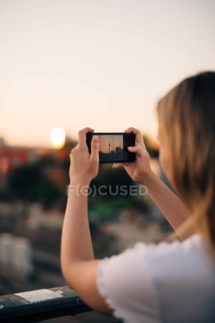 Cropped image of young woman photographing Fernsehturm through smart phone during sunset — Stock Photo