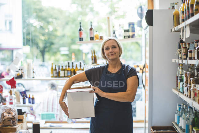 Portrait of confident female owner carrying cardboard box in deli — Stock Photo