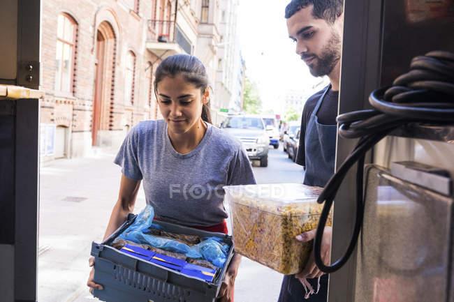 Jóvenes propietarios multiétnicos llevando comida en camión en la ciudad - foto de stock