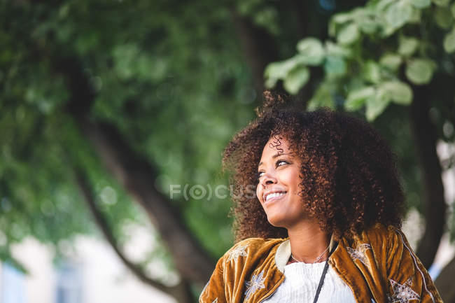 Close-up of thoughtful mid adult woman with curly hair looking away at park — Stock Photo