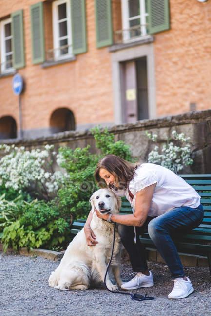 Seniorin umarmt Hund, während sie auf Parkbank sitzt — Stockfoto
