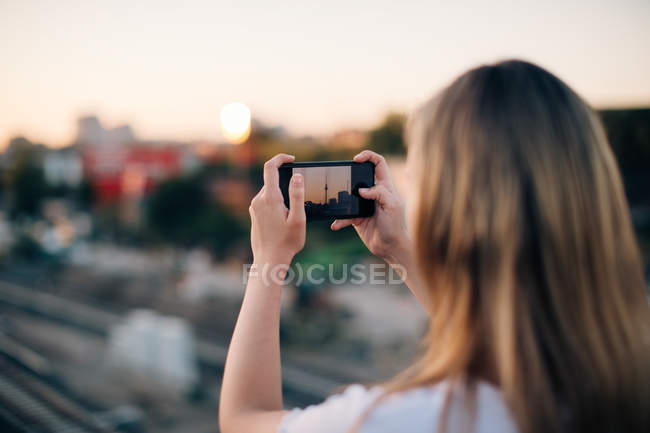 Young woman photographing Fernsehturm through smart phone during sunset — Stock Photo