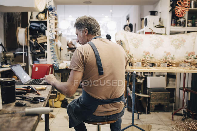 Rear view of male upholstery worker using laptop at workbench in workshop — Stock Photo